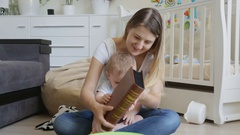 Young mother watching photographs in family album with her baby son Stock Footage