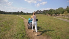 Beautiful young woman pushing pram on the path at park Stock Footage
