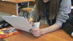 Schoolgirl sitting at a school desk on the lesson Stock Footage