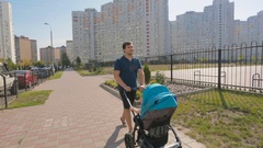 Happy young father walking with baby pram on street Stock Footage