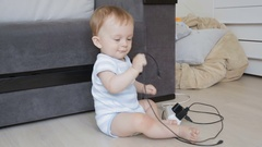 Concept of baby in danger. Toddler playing with wires and cables on floor Stock Footage