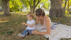 Adorable 1 year old baby boy on picnic with mother at park Stock Footage