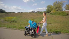 Beautiful smiling woman walking with bay son in pram at park Stock Footage