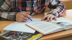 Learner writes the text in a notebook on a lesson Stock Footage