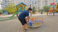 Happy young father riding his baby son on carousel at playground Stock Footage