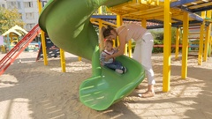 Young mother teaching her baby son how to ride on the slides at playground Stock Footage