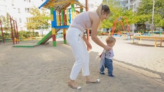CUte baby boy walking with his mother on the playground Stock Footage