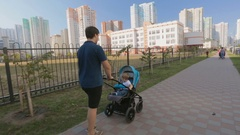 Happy young father pushing baby pram on street at sunny day Stock Footage