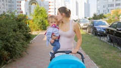 Happy smiling mother holding her baby son and pushing pram on street Stock Footage