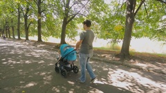 Happy young father walking with baby in stroller at park Stock Footage