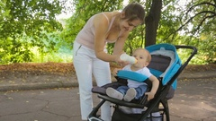 Beautiful woman feeding her baby son from bottle in pram at park Stock Footage