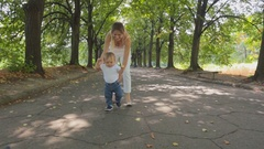 Beautiful young woman teaching her baby son walking at park Stock Footage
