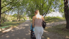 Steadicam shot of beautiful young mother walking with baby in pram at park Stock Footage