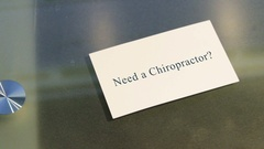 Hand puts business card on table with text Need a Chiropractor Stock Footage
