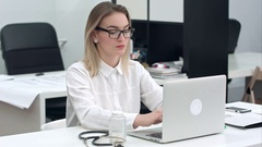 Concentrated young woman in glasses typing on the laptop at her office desk Stock Footage