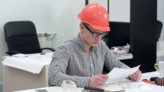 Architect working on blueprints while female colleague bringing more drawings Stock Footage
