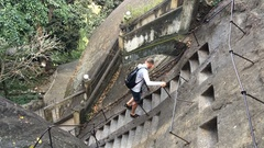 Young man comes down the stairs in the stone ancient temple Mulkirigala Stock Footage