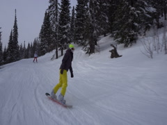 Snowboarder is riding dowm slowly from snowcovered mountains slope at clo Stock Footage