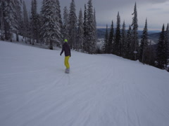 Snowboarder is riding dowm fast from snowcovered mountains slope at cloud Stock Footage