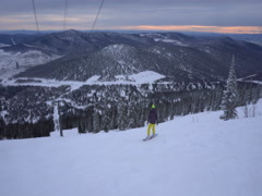 Back view woman is drifting fast on a snowboard from mountains top at clo Stock Footage