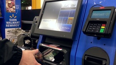 Close up of man paying foods at self-check out counter inside Walmart store Stock Footage