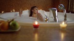 Woman relaxing with champagne in bath with foam Stock Footage
