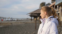 Young woman in a white jacket in the winter on the beach at sunset Stock Footage