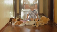 Cute smiling baby boy playing on floor with stuffed toys Stock Footage