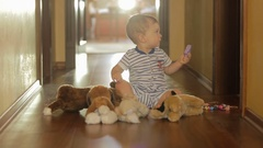 Cute 10 months old baby boy playing on floor with stuffed toys Stock Footage