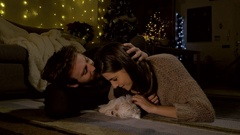 Couple in love at home at night cuddling little puppy dog on the floor wide.. Stock Footage