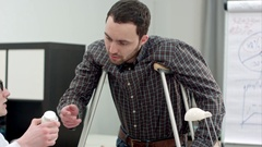 Young man with crutches looking at pills prescribed by doctor Stock Footage
