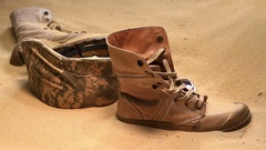 Soldier hat  boots and sand glass in the desert Stock Footage