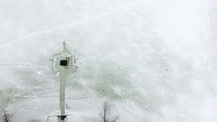 Camera flying above squared ice-hole with pathway from shore and human footprint Stock Footage