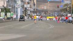 Exhausted man running toward finish on city marathon day Stock Footage
