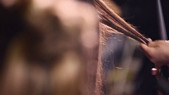 Hairdresser makes hairstyle for the model close-up. Weaving hair braids. Stock Footage