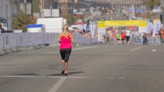 Out of focus shot of runners going to the finish line at city marathon Stock Footage