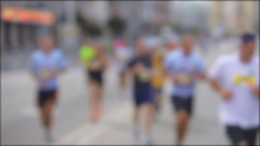 Defocused shot of rejoicing runners on finish at city marathon Stock Footage