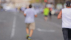 Defocused shot from back of runners group on city marathon Stock Footage