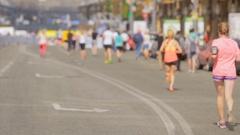 People running towards finish on city marathon day Stock Footage