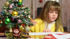 The girl draws at the table Christmas pattern, focusing on the fur-tree Stock Footage