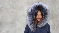 Closeup beautiful smiling girl wearing coat with fur hood in winter Stock Footage
