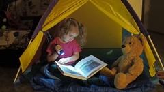 Cute little child is reading a book with flashlights in tent. Happy girl pl.. Stock Footage