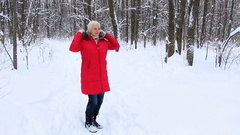 Attractive senior woman in the winter snow wood in red coat having fun Stock Footage