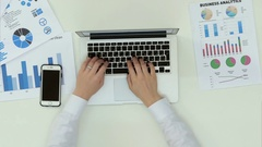 Woman's hands typing on laptop computer at office desk with statistics graph Stock Footage