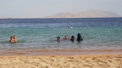 Muslim family bathes in sea Stock Footage