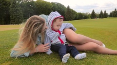 Beautiful young mother lying with her 1 year old baby son on grass at park Stock Footage