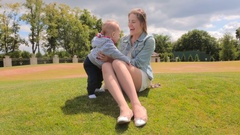 Young woman playing with her 1 year old son on grass at park at sunny day Stock Footage
