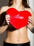 Young beautiful girl with naked body, holding a red heart pillow Stock Photos