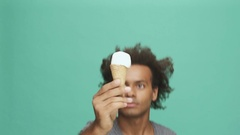 Happy afro american man eating ice cream and looking at camera Stock Footage