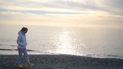 Blonde woman with long hair walks in white jacket near the sea the sea Stock Footage